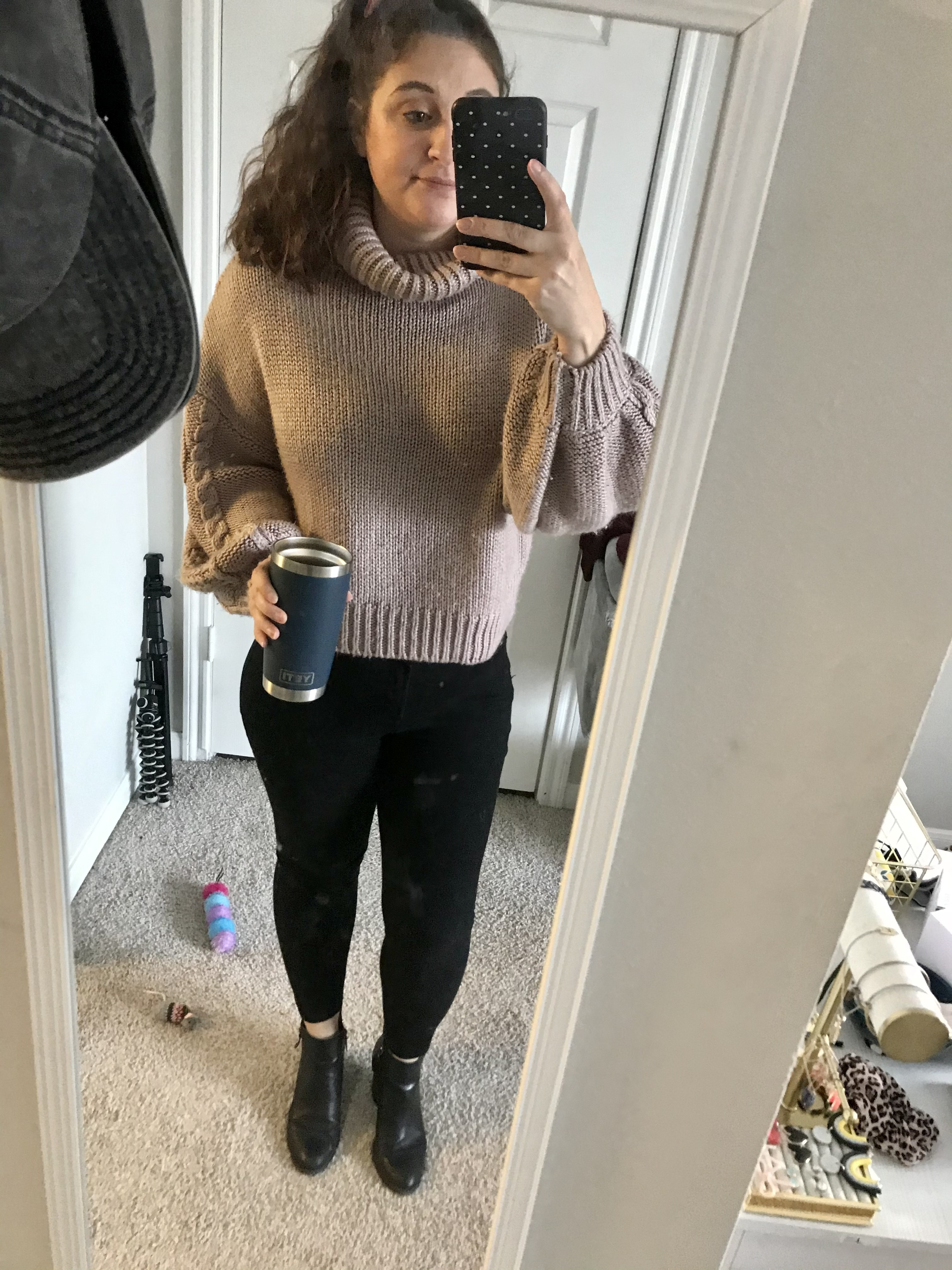 girl with hair up in purple turtleneck and black jeans