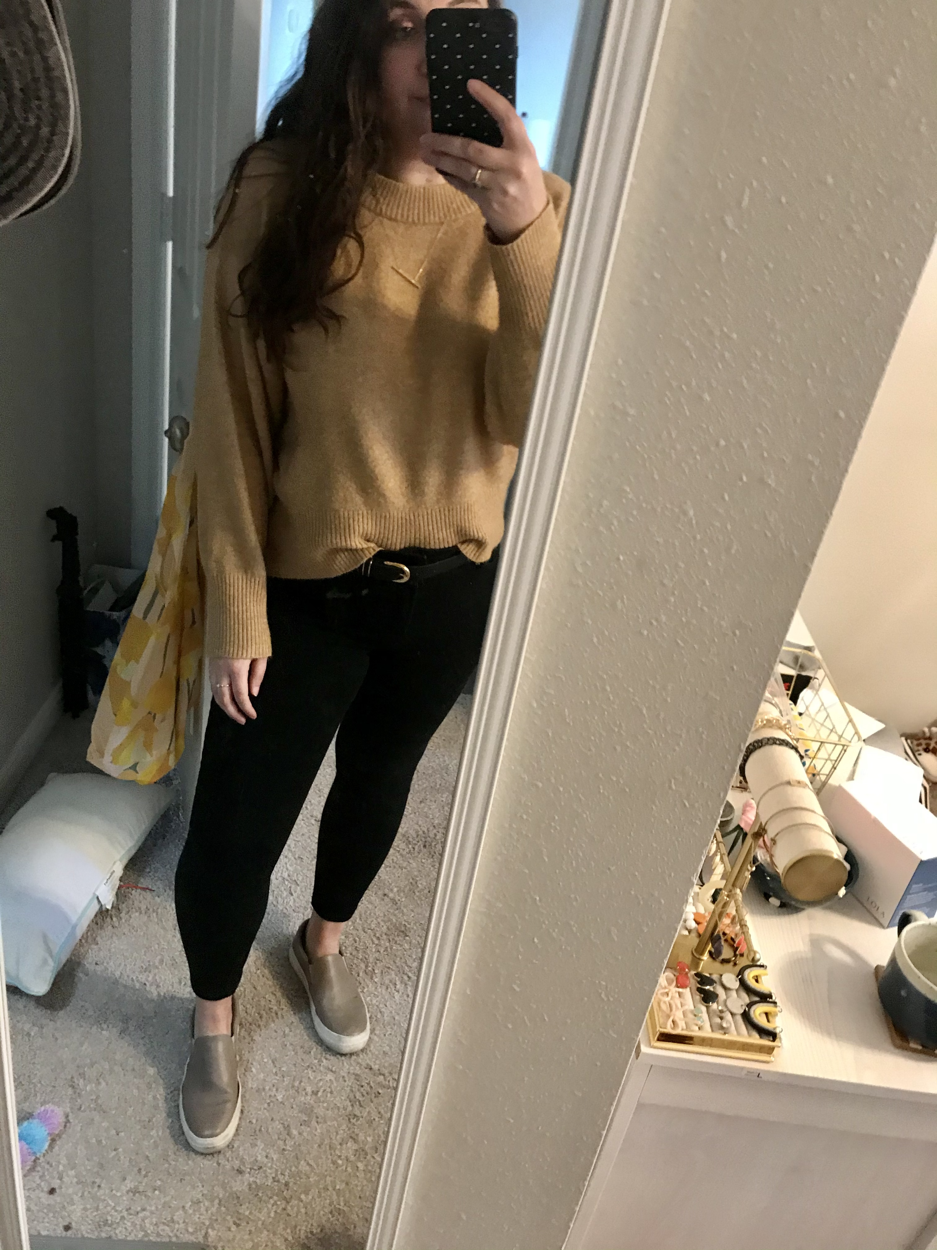 Girl in brown sweater and black jeans with grey slide on sneakers