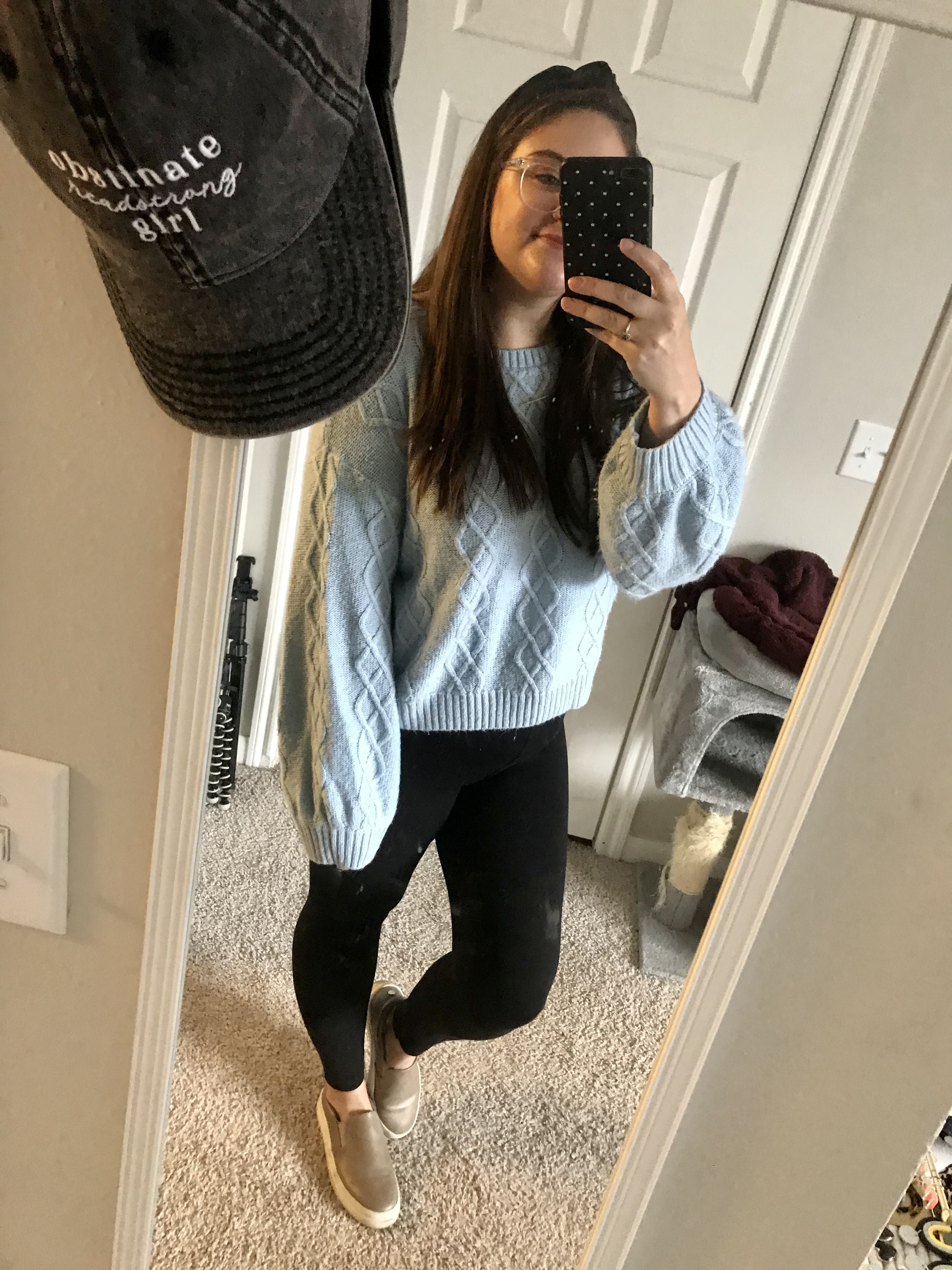 Girl in blue sweater and black leggings with grey slip on sneakers and black knot headband