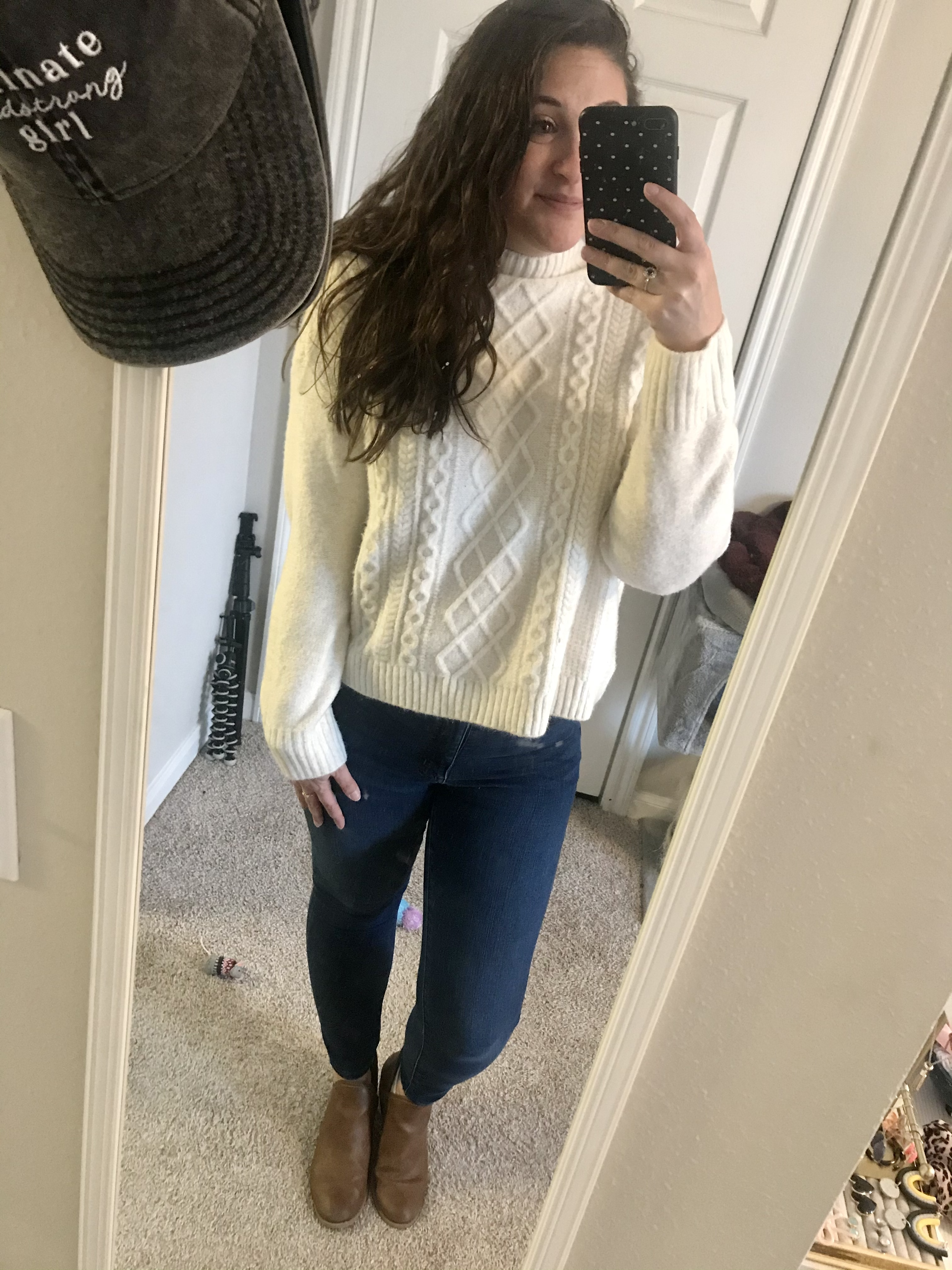 Girl in white turtleneck sweater with blue jeans and brown boots
