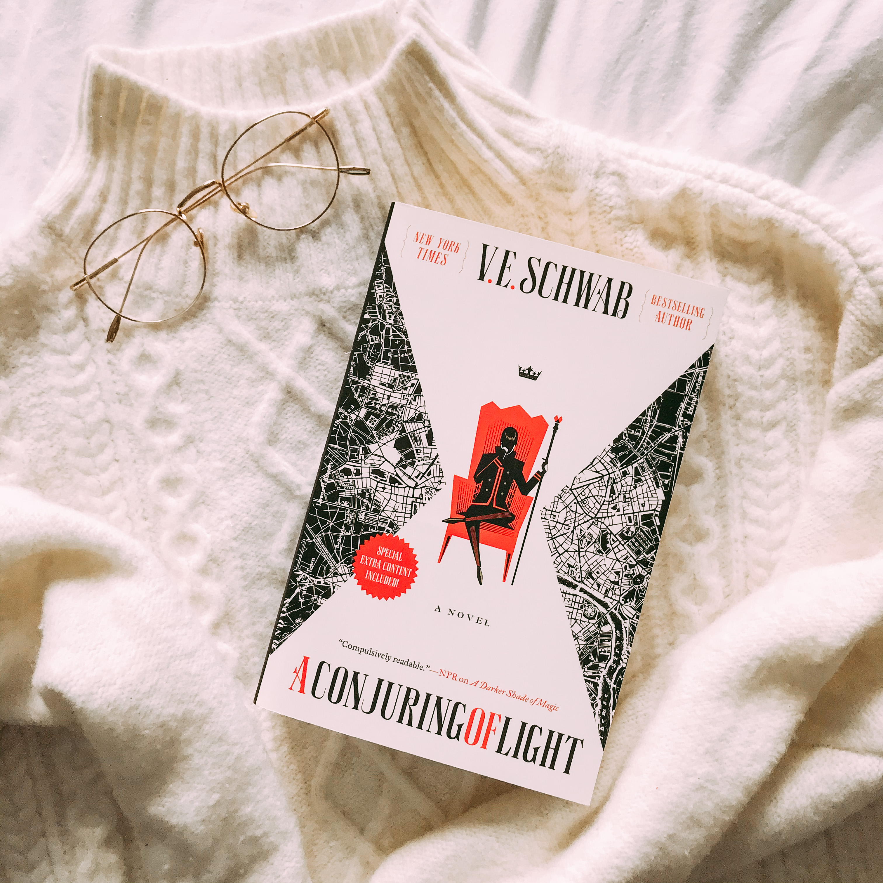 a conjuring of light book by ve schwab with a white turtleneck sweater and gold rimmed glasses